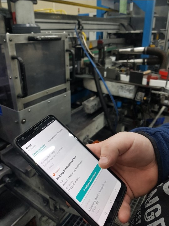 hand holding a smartphone infront of a production line